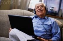 Elderly Man Listening to Music through Laptop