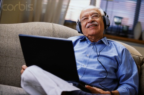 Elderly Man Listening to Music through Laptop
