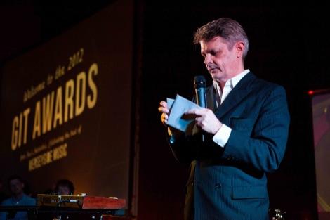 Paul du Noyer opens the envelope at the GIT Award 2012.jpg